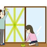 窓ガラスの台風対策をする男女